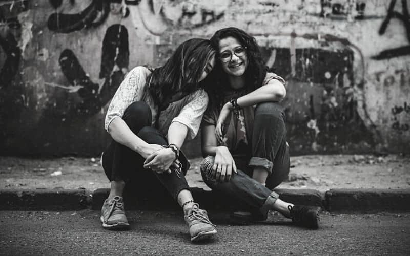 Dos amigas sentadas en una cera de la calle