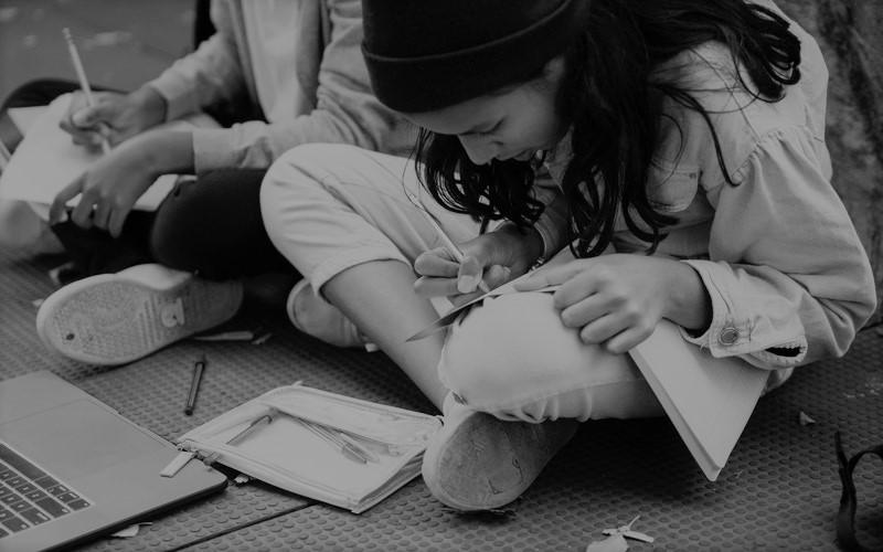 Dos jóvenes sentadas en el suelo de la calle y escribiendo en cuadernos, junto a un portatil.